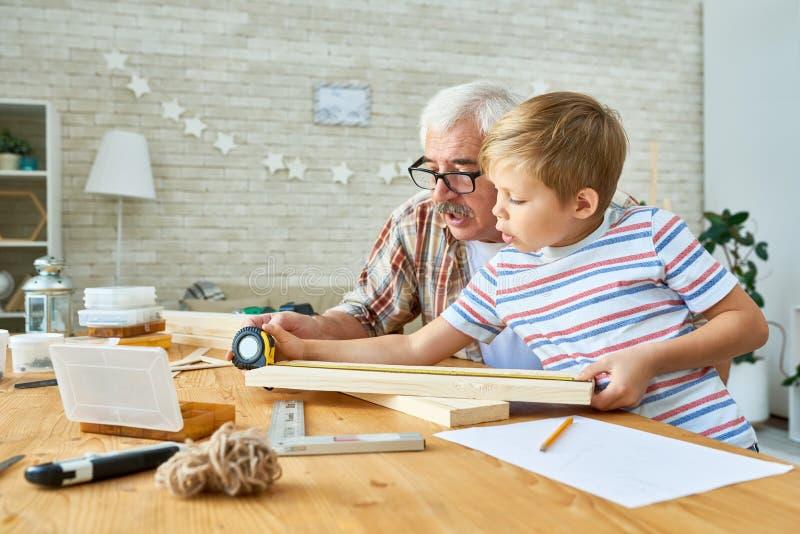 Abuelo que enseña a la carpintería de Little Boy fotografía de archivo libre de regalías