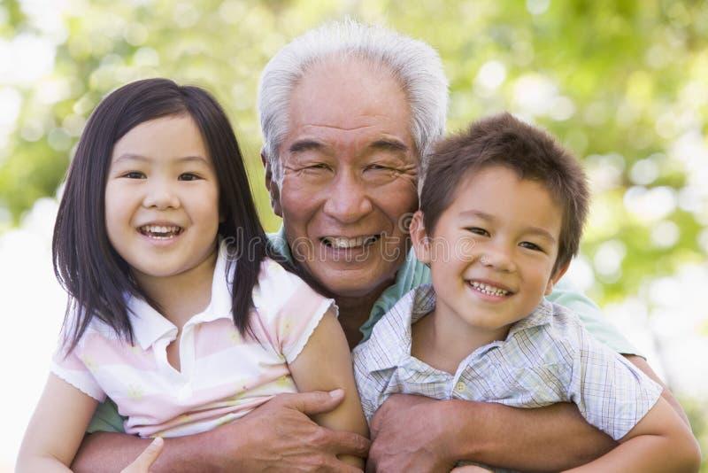 Abuelo que presenta con los nietos imagenes de archivo