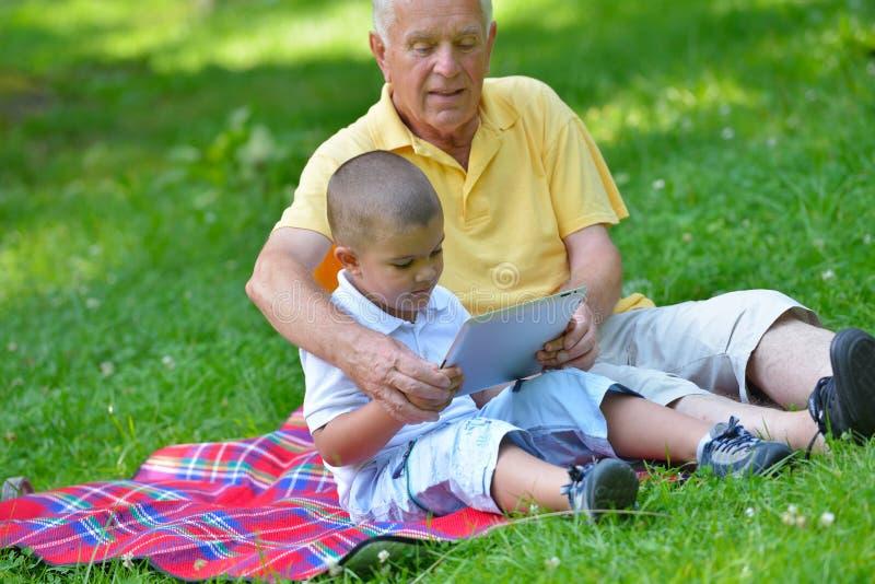 Abuelo y niño felices en parque imagenes de archivo