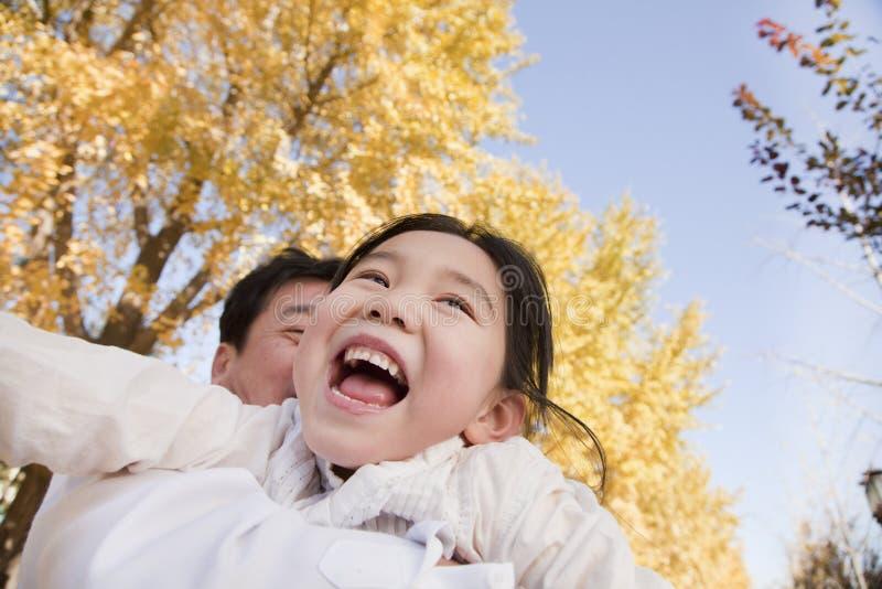Abuelo y nieta que juegan en el parque, riendo, en otoño imagen de archivo libre de regalías