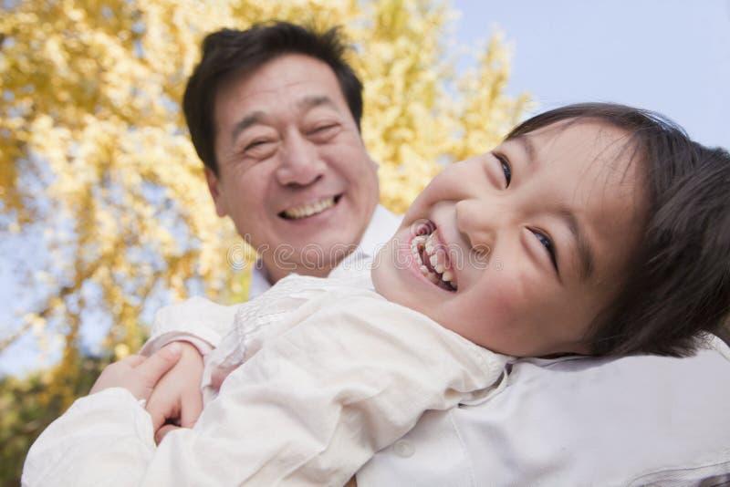 Abuelo y nieta que juegan en el parque, riendo, en otoño fotografía de archivo libre de regalías