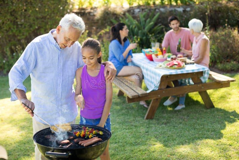 Abuelo y nieta que preparan la barbacoa mientras que familia que tiene comida imagen de archivo libre de regalías