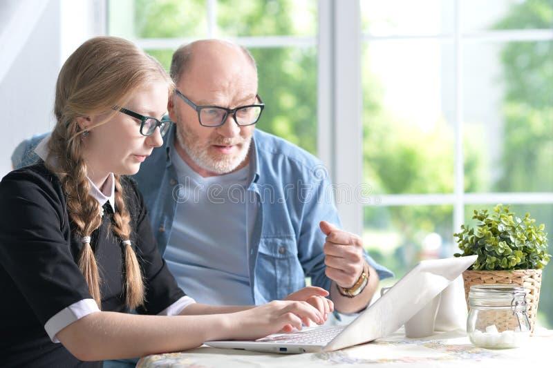 Abuelo y nieta que usa el ordenador portátil foto de archivo libre de regalías