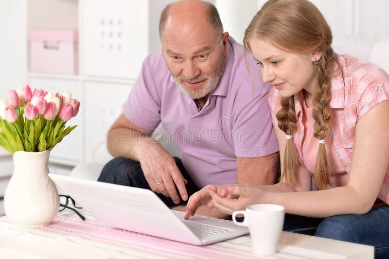 Abuelo y nieta que usa el ordenador portátil imagenes de archivo