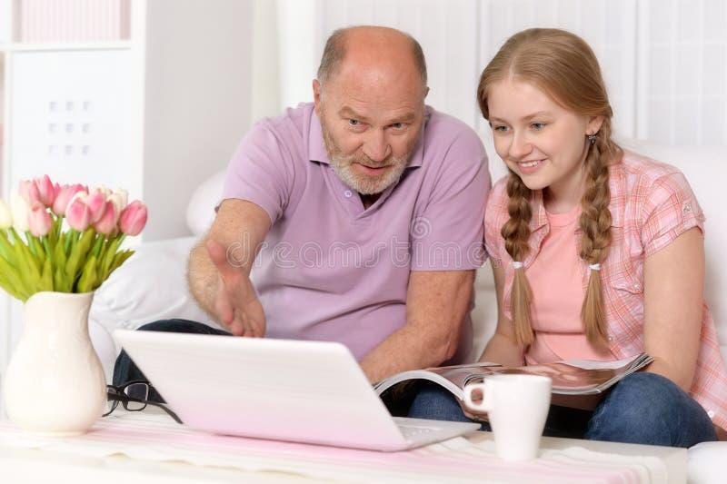 Abuelo y nieta que usa el ordenador portátil imagen de archivo libre de regalías