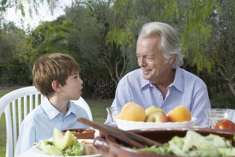 Abuelo y nieto en la tabla al aire libre foto de archivo