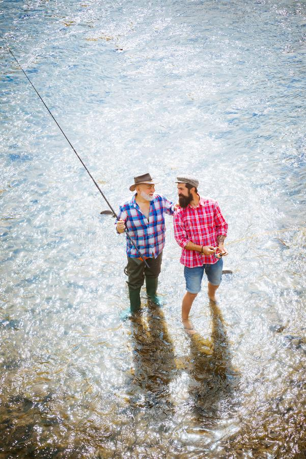 Abuelo y nieto felices con las cañas de pescar en litera del río Concepto de familia feliz - padre e hijo junto Mosca fotografía de archivo