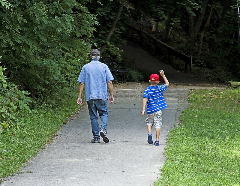 Abuelo y nieto que caminan en parque imagen de archivo