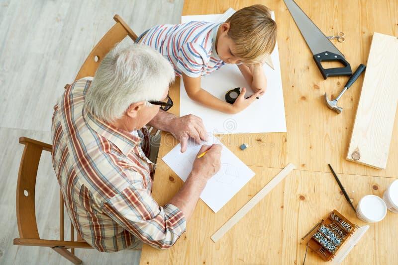 Abuelo y nieto que hacen la pajarera imagenes de archivo