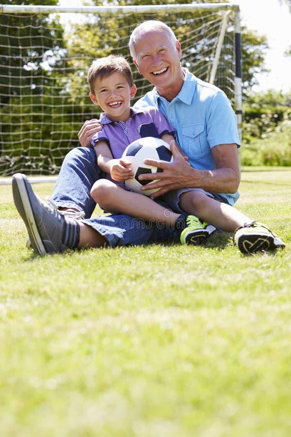 Abuelo y nieto que juegan a fútbol en jardín foto de archivo