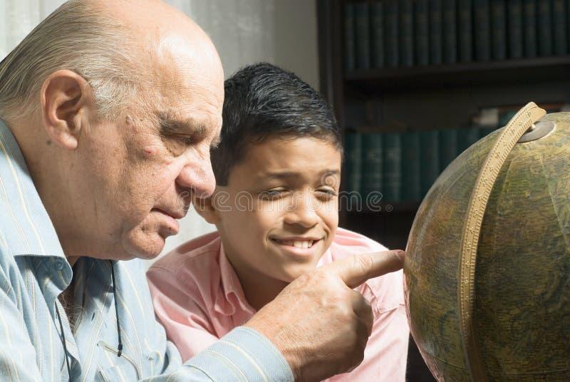 Abuelo y nieto que miran el globo imagenes de archivo