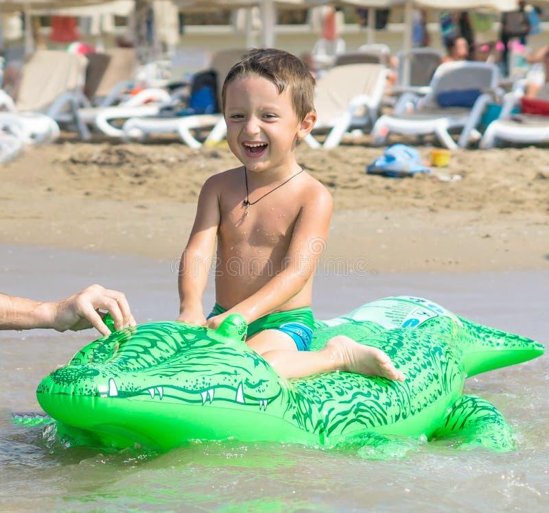 Abuelo y nieto sonrientes que juegan y que salpican en la agua de mar Retrato del muchacho feliz del niño en la playa del océano  imagenes de archivo