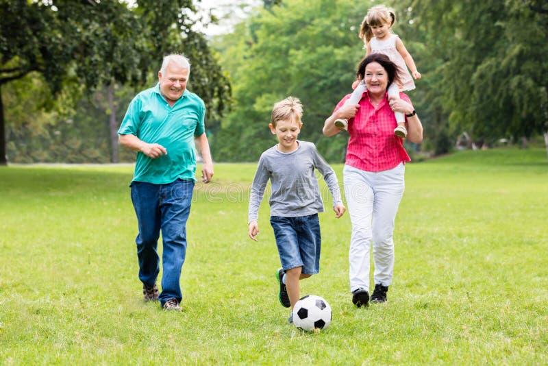 Abuelo y nietos que juegan el balón de fútbol junto foto de archivo libre de regalías