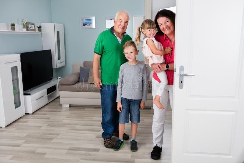 Abuelo y nietos que se colocan detrás de puerta fotografía de archivo