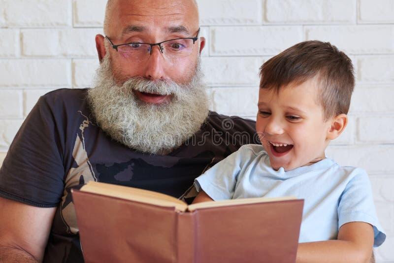 Abuelo y su nieto que pasan el tiempo junto que lee un fu foto de archivo
