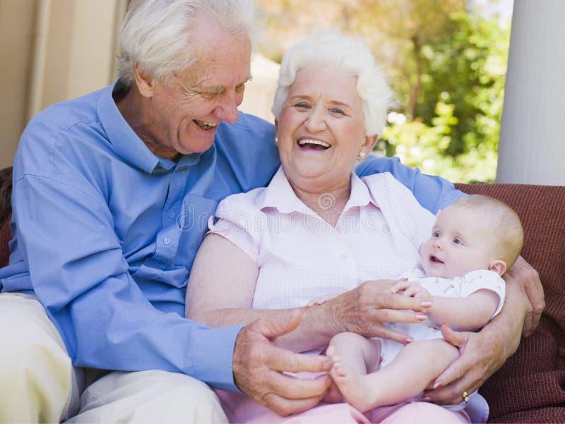 Abuelos al aire libre en patio con el bebé imagen de archivo libre de regalías