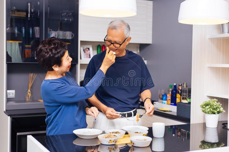Abuelos asiáticos mayores de los pares que cocinan junto mientras que la mujer está alimentando la comida al hombre en la cocina fotos de archivo