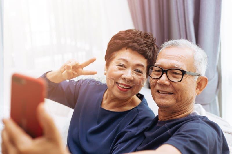 Abuelos asiáticos mayores de los pares que toman una foto del selfie junto en casa fotos de archivo libres de regalías