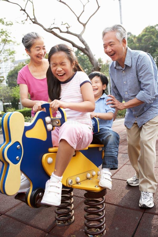 Abuelos chinos que juegan con los nietos imagenes de archivo