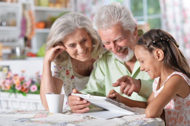Abuelos con la nieta que usa el ordenador portátil imagen de archivo