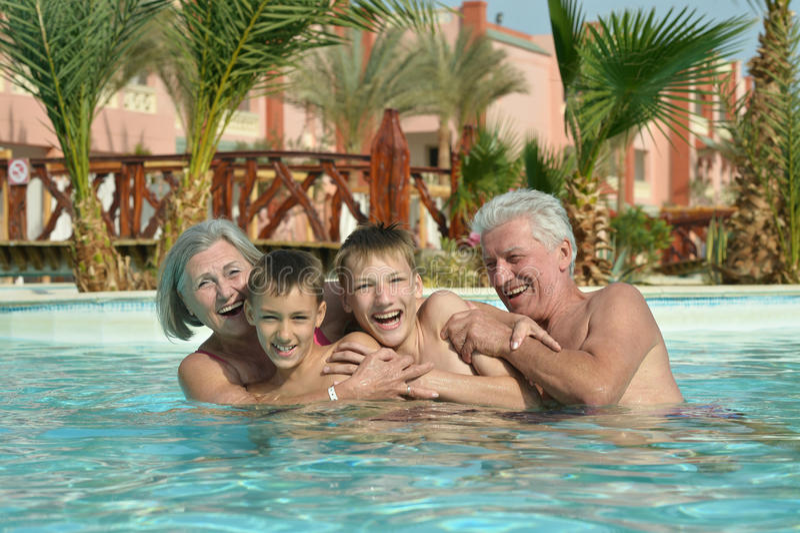 Abuelos con los nietos en piscina imágenes de archivo libres de regalías