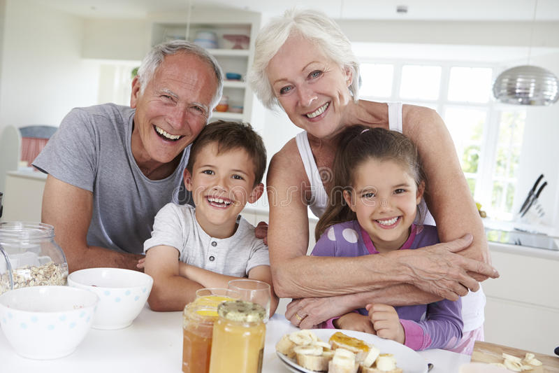 Abuelos con los nietos que comen el desayuno en cocina imágenes de archivo libres de regalías