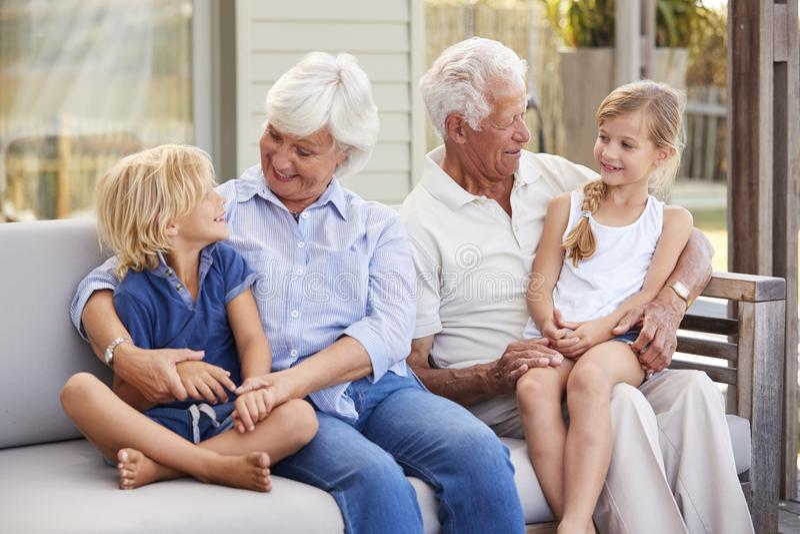 Abuelos con los nietos que se relajan en cubierta en casa imagen de archivo