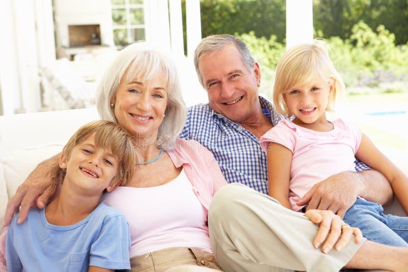 Abuelos con los nietos que se relajan junto imagen de archivo