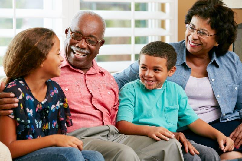 Abuelos con los nietos que se sientan en el sofá y hablar fotos de archivo libres de regalías