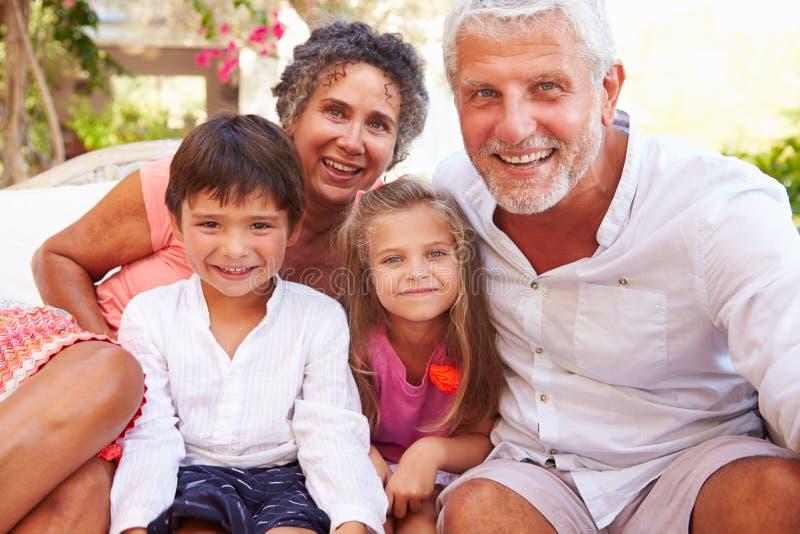 Abuelos con los nietos que se sientan en Seat en ½ del ¿de Gardenï imagen de archivo libre de regalías