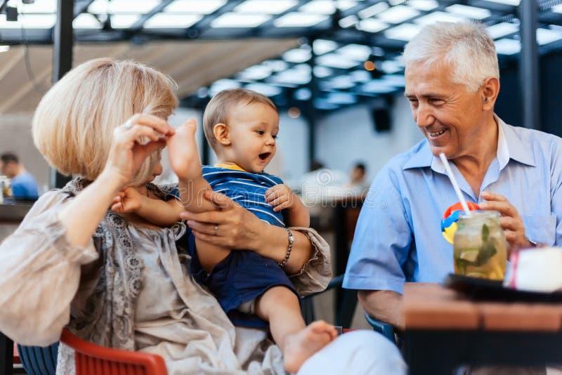 Abuelos con su nieto en el café foto de archivo