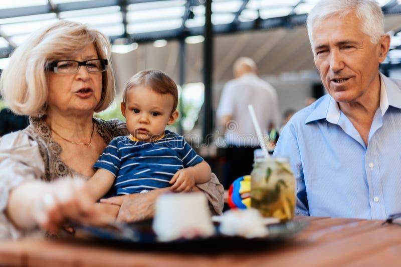 Abuelos con su nieto en el café fotografía de archivo