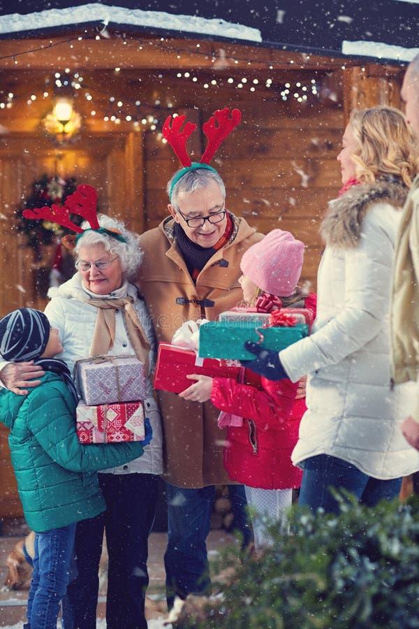 Abuelos del día de fiesta de la Navidad que recolectan a niños en la Navidad imagen de archivo