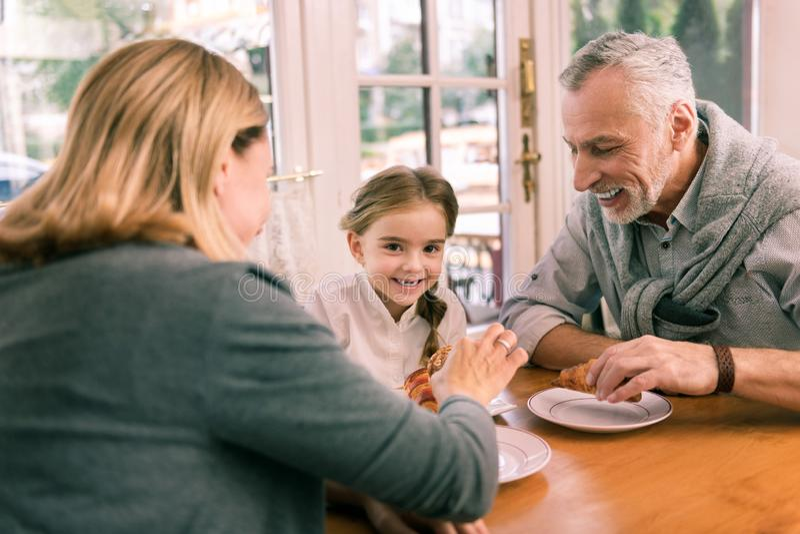 Abuelos felices que llevan a su pequeña nieta linda a la panadería foto de archivo libre de regalías