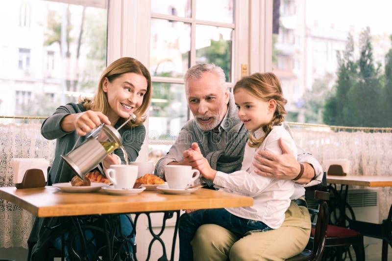 Abuelos felices y niña linda que desayunan en cafetería fotos de archivo