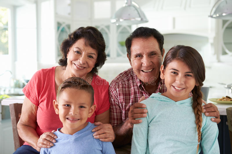 Abuelos hispánicos en casa con los nietos imagen de archivo libre de regalías