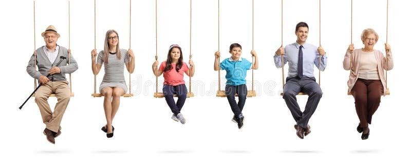 Abuelos, padres y niños sentándose en oscilaciones y sonriendo en la cámara foto de archivo