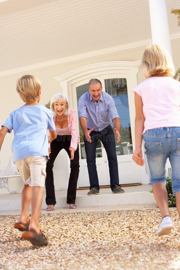 Abuelos que acogen con satisfacción a nietos en visita foto de archivo libre de regalías