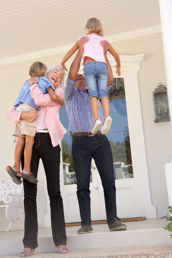 Abuelos que acogen con satisfacción a nietos en visita imagenes de archivo