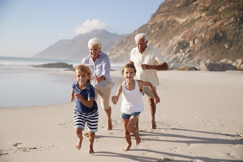 Abuelos que corren a lo largo de la playa con los nietos el vacaciones de verano fotografía de archivo