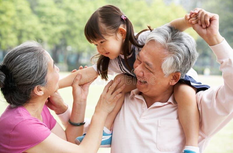 Abuelos que dan paseo de la nieta fotos de archivo