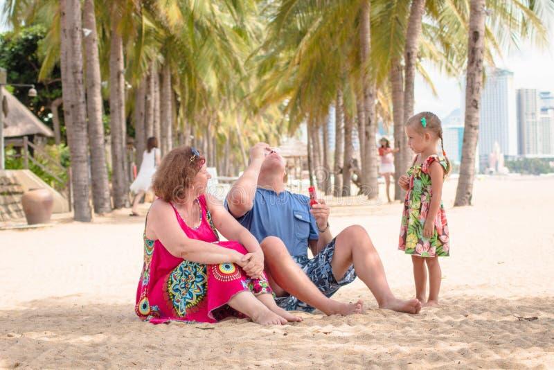 Abuelos que disfrutan de día con la nieta mientras que sopla burbujas de jabón en la playa cerca del mar fotos de archivo