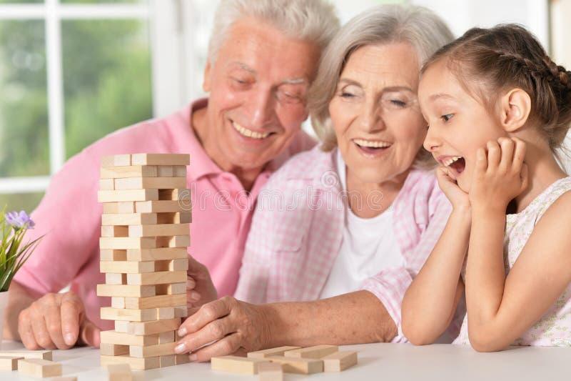 Abuelos que juegan con su pequeña nieta fotos de archivo