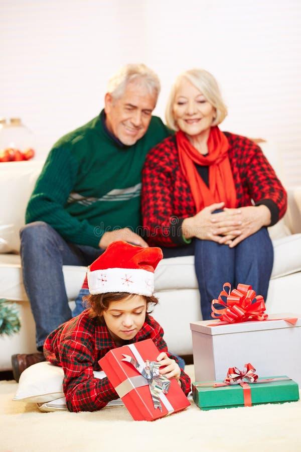 Abuelos que miran los regalos de la Navidad de la abertura del nieto foto de archivo libre de regalías
