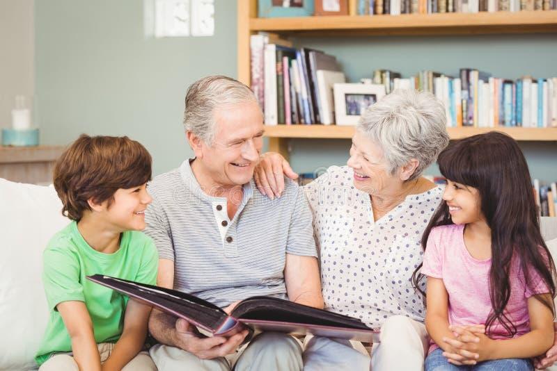 Abuelos que muestran el álbum a los nietos fotos de archivo libres de regalías