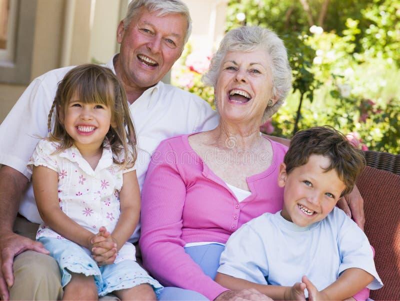 Abuelos que ríen con los nietos imagen de archivo