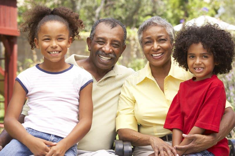 Abuelos que se relajan en jardín con los nietos imagen de archivo