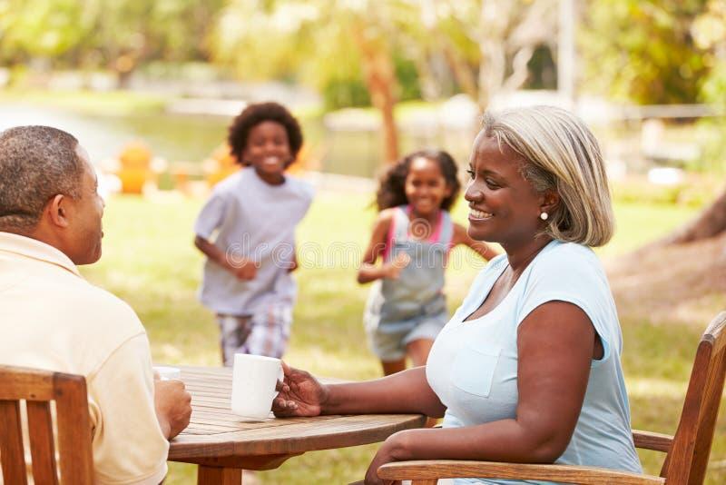 Abuelos que se relajan mientras que los nietos juegan en jardín imagen de archivo libre de regalías