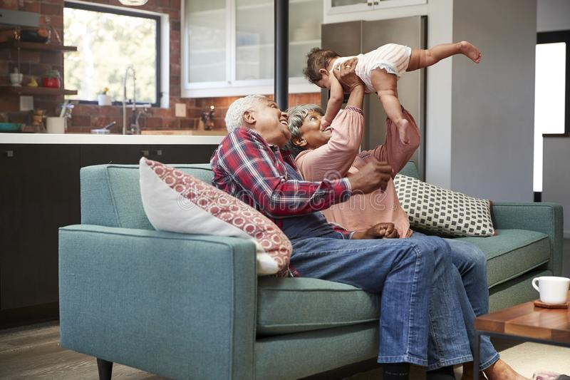 Abuelos que se sientan en Sofa Playing With Baby Granddaughter en casa fotos de archivo