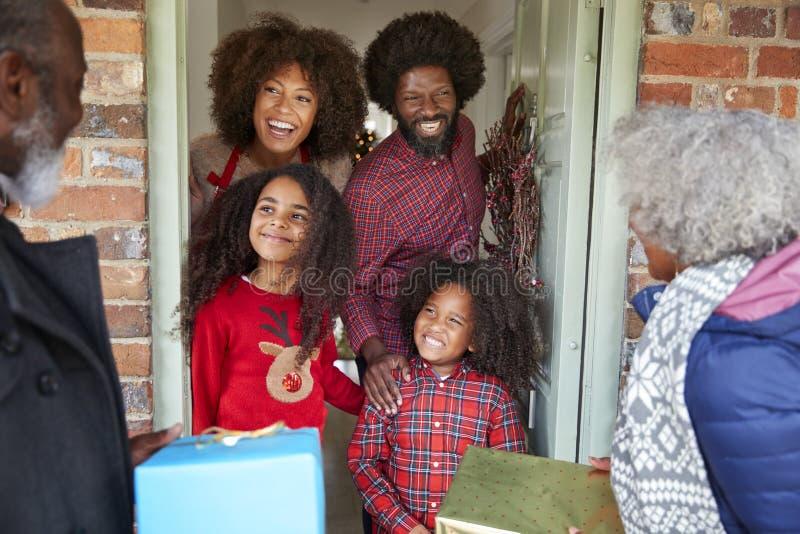 Abuelos que son saludados por la familia como llegan para la visita el día de la Navidad con los regalos imagen de archivo libre de regalías